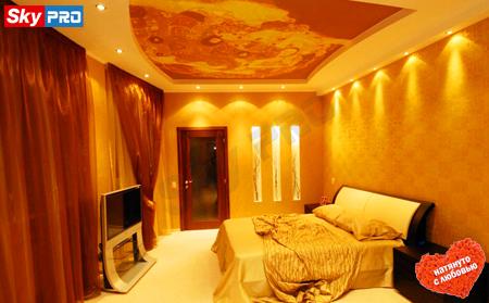 Оранжевый натяжной потолок с точечными светильниками в спальне